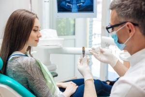 Dentist showing patient dental implant model
